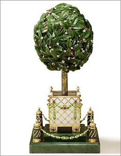 Orange Tree Egg (Bay Tree Egg    Presented by Tsar Nicholas II to the Dowager Empress Maria Feodorovna on Easter 1911, a silver gilt key allowed the Dowager Empress to discover the surprise hidden within the egg-shaped topiary tree. Tucked within the finely engraved nephrite leaves, enameled flowers and jeweled fruit is a gold winding mechanism. When triggered, a portion of the foliage at the top of the tree rises. Suddenly, music fills the air lapping its wings.