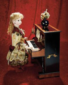 """Rare and Luxurious French Musical Automaton    20"""" (51 cm.) doll h. Standing at the keyboard of an elegant rosewood and ebony upright piano is a bisque-head doll with bisque shoulder plate,brown glass paperweight inset eyes,dark eyeliner,lushly-painted lashes and brows,accented nostrils,closed mouth,pierced ears,blonde mohair wig over cork pate,carton torso and legs,wire upper arms,papier-mache hands,elegant silk costume."""