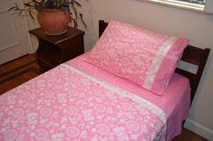 Jogo de Cama Solteiro, confeccionado em tecidos 100% algodão, de luxo (Maluhi) <br>Inclui 3 peças: <br>- 1 Lençol de elástico medindo 1,90m x 0,90m x 0,17m <br>- 1 Lençol de cobrir com vira feita, com bordado inglês e fita de cetim medindo 2,20m x 1,50m <br>- 1 Fronha combinando com a vira do lençol de cobrir, com bordado inglês e fita de cetim, medindo 0,70m x 0,50m