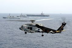 An SH-60F Seahawk helicopter is airborne while different countries military ships participate in an exercise.