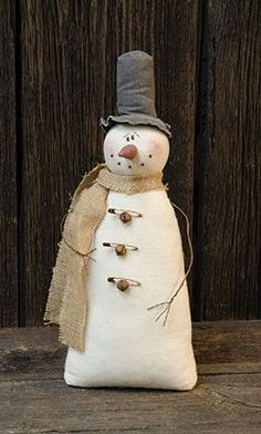 "Made of soft fabric, the Vintage Snowman has wire arms and a burlap scarf with rusty bell and safety pin accents. Measures 18"" high and 7¼"" wide."