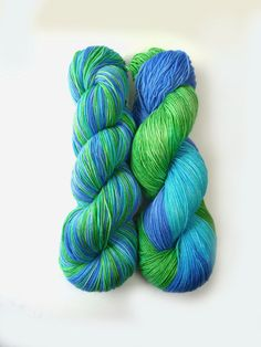 Sock yarn hand dyed yarn in periwinkle blue, spring green, and a light teal. The first photo shows this yarn reskiend on the left and as dyed on