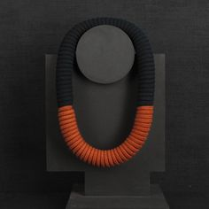 This Eleanor Bolton necklace is a limited edition especially for Darkroom's Aztec Camera season. The necklace is handmade from 100% cotton rope which has been hand-dyed in the bold combination of black and rust for statement effect. The cotton rope has been coiled and hand sewn together to create a hollow form which makes the necklace surprising light-weight despite it's size. This necklace is handmade in London.