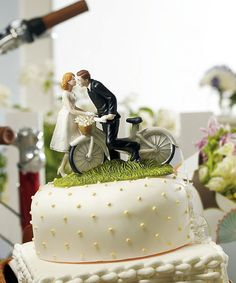 <p> This Couple is ready to pedal their way down the road to romance. The old fashioned bicycle and basket, and the Bride's knee-length dress add just the right amount of vintage flair to this playful Cake Topper. Hand painted porcelain. Please note: The hair color or colors you have requested may not be an exact match to your natural hair color and a...