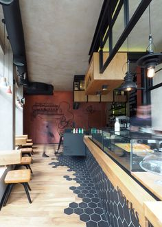 This modern coffee shop has black hexagon tiles that wrap around from the counter down to the laminate wood flooring.