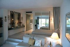 http://studioapt.files.wordpress.com/2008/07/miraflores-studio1.jpg      curtain and mirror section off the bedroom nicely