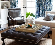 Ottoman Empire ~ Looking for an alternative to a coffee table? Try anchoring a living room with an oversize cocktail ottoman. It becomes an entertaining piece when topped with trays, and it will naturally complement upholstered seating in any style.