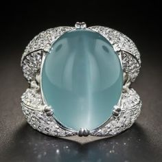A rare and exotic gemstone: a cabochon aquamarine imbued with shimmering chatoyancy (i.e. the cat's-eye effect), weighing 23.76 carats, casts an enchanting soft velvety blue glow, supported by a sparkling, pave'-set diamond split ring shank, in this big, bold and uniquely beautiful bauble rendered in gleaming platinum. 2.77 carats total diamond weight, 7/8 by 1/2 inch, currently ring size 6.