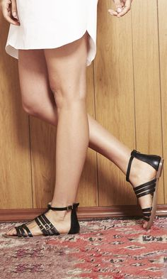 Black strappy gladiator sandals with an easy back zipper and gold-toned hardware