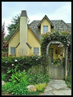 Yellow cottage with cute garden gate