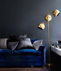 Deep blue velvet sofa, dark grey walls, gold coloured spherical floor lamp