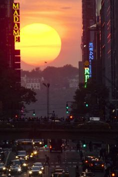 People take pictures of the sunset on 42nd street during the biannual occurrence named Manhattanhenge in New York City