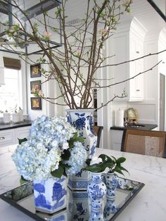 lovely spring vignette...LOVE the collection of blue and white showcased in this AMAZING all white kitchen