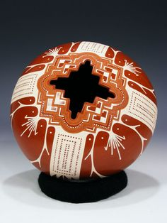 Mata Ortiz Hand Coiled Pottery by Angel Amaya. This beautiful piece was hand made by Angel Amaya. It is deep red accented with cream colored geometric designs. It is hand coiled and signed by the artists. Includes pottery ring stand.