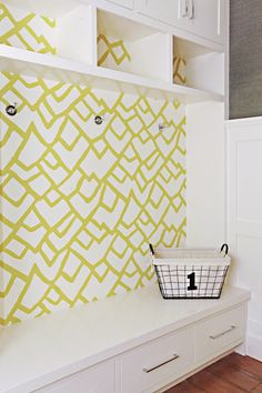 Chic mudroom features white built-in cabinets atop cubbies paired with built-in bench with wallpapered backsplash covered in Schumacher Zimba Wallpaper in Soft Chartreuse. Laundry Room Wallpaper, Wallpaper Shelves, Fabric Wallpaper, Of Wallpaper, Mudroom Laundry Room, Laundry Room Remodel, Cabinet Decor, Cabinet Design, Modern Laundry Rooms