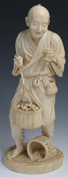 JAPANESE CARVED IVORY ELDER MERCHANT WITH EGGS Japanese carved ivory elder merchant. Finely carved with intricate detail. Merchant is weighing eggs for sale and has a basket of grapes at his feet. His facial expression shows his happiness in his work. Signed on base. Weight: 1600g Size: 12""