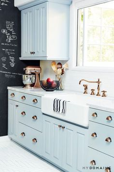 Chic kitchen with baby blue cabinets, brass hardware, and a chalk wall