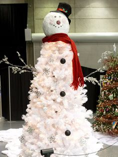 Frosty the Snowman Christmas Tree:   Celebrate the season anew with a Frosty the Snowman-inspired Christmas tree. Craft or buy a papier-mache snowman head and place atop a white artificial Christmas tree. Space three black ornament balls down the center to create buttons, secure silver branches to the middle for arms, and position rain boots under the base to create feet.  Finish by wrapping a red scarf underneath Frosty's head and embellishing all over with transparent ornament balls and si...