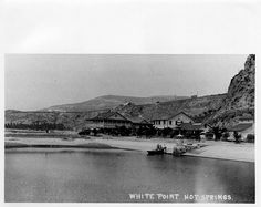 "White's Point Hot Springs  (also known as ""White Point"") hotel, restaurant, and guest  cabins. A group of people is launching a dory off the beach in  foreground."