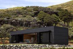 Lo studio Fearon Hay Architects ha progettato la casa vacanza Storm Cottage, nell'Isola Great Barrier, in Nuova Zelanda. Esempio di architettura minimale ed ecosostenibile.