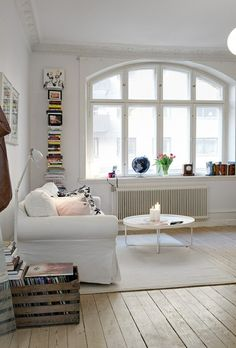 I love the window, high ceiling, molding, the floors, the whites and light…. calm and energized at the same time. I'd prefer a wood coffee table, though.