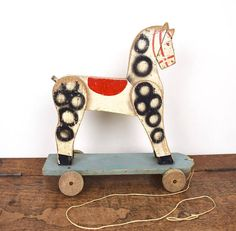 Vintage toy wooden pull-along horse on wheels.