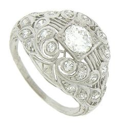 $4600 This magnificent antique platinum engagement ring features an ornate design of curling organic cutwork, intricate engraving and mil grain frosted filigree. Diamond frosted petals twirl around the rings shoulders and sides framing the central mounting. The square mounting is set with a .84 carat, F colored, Vs2 clarity round cut diamond. This stunning Edwardian ring measures 13.72 mm in width. Circa: 1910. Size 4 1/2. We can re-size slightly.