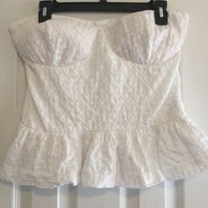 Strapless Peplum Top Lace like material. Brand new. Never been worn. Bought it and it didn't fit and I lost the receipt . No stains or holes. Has bra pads inside it and the grips that keep it up. Perfect for a party. Very cute. Rampage Tops