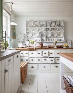 vintage white kitchen. I adore the plates on the wall and those apothecary drawers !