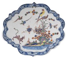 A Dutch Delft polychrome plaque, early 18th century -  Of lobed quatrefoil shape depicting a purple tiger scaring off two birds in flight, three other colourful birds perched on flowering bamboo, prunus and peony branches sprouting from colourful rockwork under banded hedges, the shaped border with a blue and white pattern of scrollwork leaves alternated by trellis and single flowers,  32.5cm diam