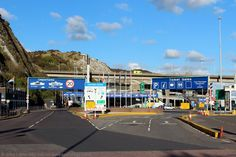 Entrance to Ferry Terminal, Eastern Docks, Dover Harbour, Kent, England, UK. Ticket Sales, Arrivals and Departures lounge for foot passengers at the base of White Cliffs of Dover. Cross-English Channel ferry operators: P and O Ferries, DFDS Seaways (Norfolk Line), and MyFerryLink (ex-SeaFrance ships). Port of Dover Police Station on left.  Dover Coastguard Station Microwave Tower on cliffs above ambulance on A2 Jubilee Way bypass. Travel and Tourism. See…