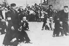 Jewish men are publicly humiliated in the market square of Minsk Mazowiecki by being forced to race against one another while riding on the backs of their fellows.     These Jews were selected from a larger group (the spectators in the background) that was rounded up by Germans in the streets surrounding the market square. The Germans also assembled a group of Poles to watch the spectacle (not pictured).