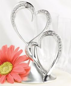 """Sophistication, style, and romance come together to create this graceful Silver Double Heart Cake Topper! This sparkling heart wedding cake topper features polished silver plating and two hearts that flow from a sleek and elegant base. Over 30 rhinestone crystals, each one framed by a delicate accent, decorate a curve on each of the hearts for a radiant flourish that's as charming as it is contemporary. Double Hearts Cake Topper measures 5-1/2"""" tall. Base measures 3-1/4"""" in diameter. Tip…"""