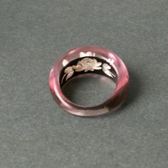 Reverse carved lucite ring with a delicate rose on a jet black background. During and after World War 2, panels cut from retired fighter plane windows were used to make these amazing reverse carved jewelry pieces. The back of the plastic was carved in elaborate florals, at times tinted, filled in, and sometimes, finished with striking contrasting backgrounds.