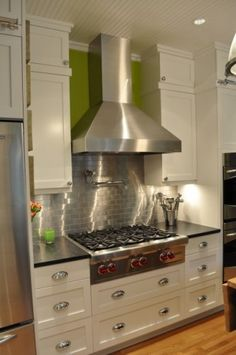 WAY fancier kitchen remodel than we're considering, but we LOVE the stainless backsplash behind the stove.