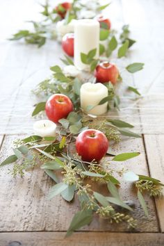 Simple apples become sophisticated when cushioned by seeded eucalyptus and pillar candles, as in this easy centerpiece by Julie Blanner.