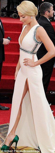 All white on the night: Margot Robbie flashed the flesh in a plunging white gown split to the thigh with beaded detail on the waist and shou...