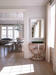 House Tour: Cape Cod. View toward dining room. Light coloured floors are perfection, as is the beautiful table and mirror vignette.