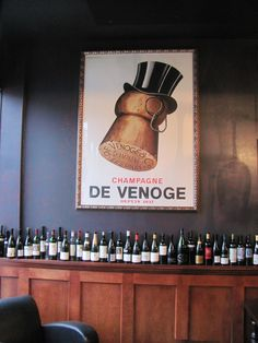 A Fabulous 1930's French Champagne Poster above the bar of a wine tasting room at a Chicago Wine Shop! Note the clean design of the poster paired with a vintage frame!