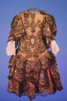 Costume worn in private court performances, mid 18th century, Museum no. S.792-1982. Pink and gold tinsel brocadeskirted with short tri-part sleeves over fitted silk sleeves, decorated in raised gold strip embroidery and braiding in elaborate stylized design with central medallions.