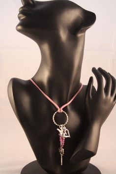 Diese Kette besteht aus einem rosa Lederimitatband, einem silberfarbenden Ring (ca. 2,7 cm), an diesem befindet sich ein Herzanhänger ( ca. 1,8 cm)...