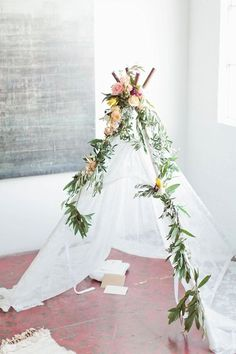 Floral garland topped teepee: http://www.stylemepretty.com/living/2016/03/03/modern-baby-shower-you-are-loved-calligraphy-backdrop/ | Photography: Callie Hobbs - http://www.calliehobbsphotography.com/blog/:
