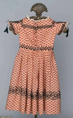 Child's Printed Wool Dress Of Fine Peach Wool, Maroon Print, Black Soutache Braid, Short Bell Sleeves With Top Lacing Over Brass Buttons, Front Closure And Muslin Bodice Lining   c.1850's