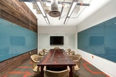 I like the mixture of textures here. The modern carpet to wood accent wall to glass whiteboards with a blue backing.