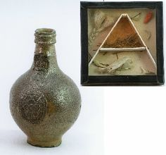 Bellarmine Jar Witch Bottle - a brown ceramic jar with a face on the side, originally containing pins, hair, nail clippings, bird bones and a red (coral?) hand, now displayed separately in a glass-fronted box. Counter-magic to reverse a curse.