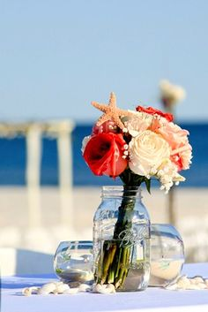 Beach #wedding table #arrangements -- bouquet flowers plus a few candles and some shells scattered down the middle. Simple & perfect. :)