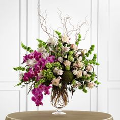 The FTD® Soft Sophistication™ Arrangement is a presentation of cultivated taste and unmatched elegance. Pale pink roses, variegated pink double lisianthus, pink veronica, pale pink peonies, purple phalaenopsis orchids, Bells of Ireland, green hydrangea, viburnum stems and curly willow branches are artfully arranged in a 16-inch footed glass vase to create an amazing display of grace and beauty.