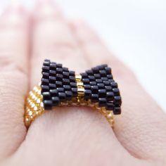 Su un evento de gala, un anillo de lazo negro en el dedo que es! Nuestro anillo de cuentas arco negro está goteando con glamour con negro brillante y reluciente oro, un pedazo de conversación definido.  © Un OOAK diseño hecho a mano por el tuyo, JeannieRichard - - - - - - - - - - - - -