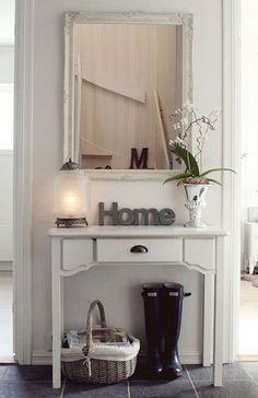 Vista frontal de un hall de entrada con un arrimo blanco, un cajón, con una lámpara y una planta encima, un espejo de marco blanco estilo rococó y bajo el arrimo un canasto con revistas y unas botas de agua.