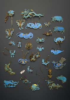 A COLLECTION OF SMALL CHINESE GILT METAL AND KINGFISHER FEATHER APPLIQUES, QING DYNASTY (1644–1912), Variously formed as bats, birds, dragons, fish, insects and other creatures and decorated with feathers, small coral beads, pearls and coloured stones, 9cm max. (30)